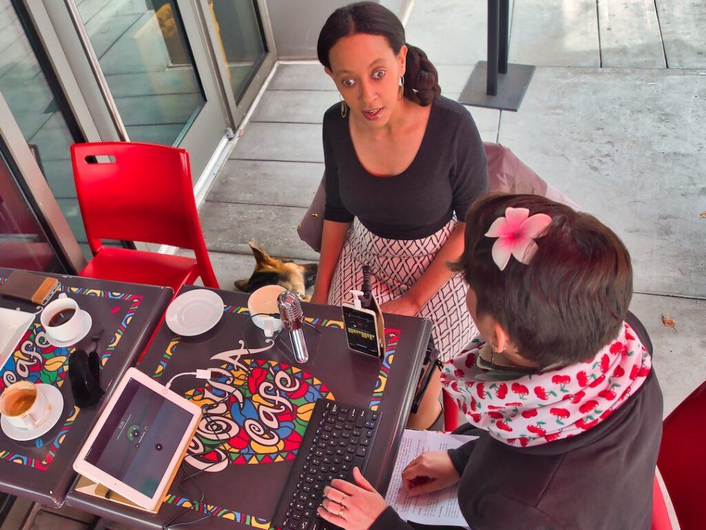Ein Blick von schräg oben auf den Tisch an dem Haben und Karina sitzen. Ein Aufnahmegerät, eine Tastatur mit kleinem Monitor und Kaffeetassen stehen auf dem Tisch.