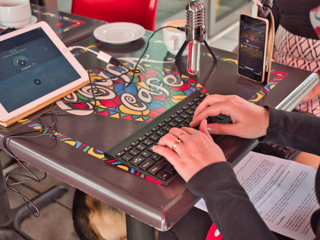 Zwei hände tippen auf einer Tastatur, die mit einer Braille-Zeile verbunden ist.