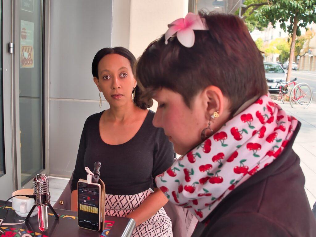 Haben Girma und Karina Sturm sitzen in einem Cafe an einem Tisch. Haben hat kinnlange dunkelbraune Haare. Karina hat kurze schwarze Haare und trägt eine Blume im Haar.