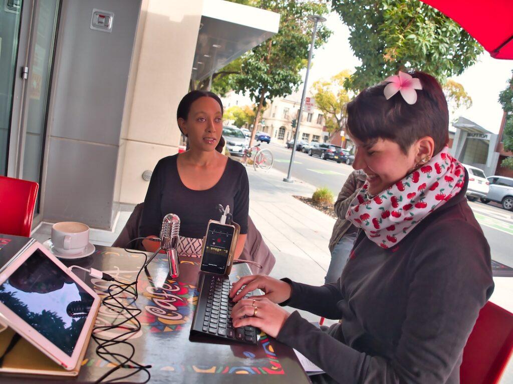 Haben Girma und Karina Sturm sitzen in einem Cafe an einem Tisch. Karina tippt konzentriert auf einer Tastatur.