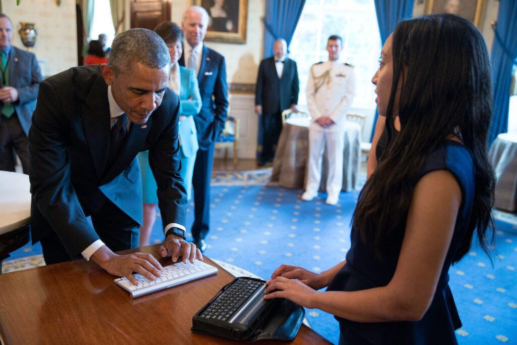 Der damalige US-Präsident Barack Obama schreibt etwas auf eine Tastatur. Haben sitzt vor ihm am Tisch und hat ihren Finger auf der Braille-Zeile.