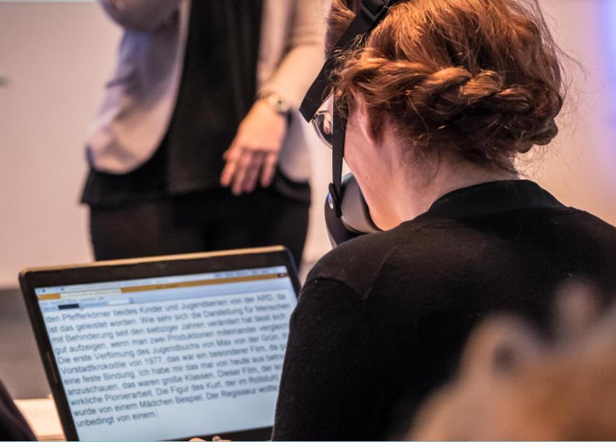 eine weiße schriftdolmetscherin sitzt am laptop und schreibt, sie ist von hinten zu sehen