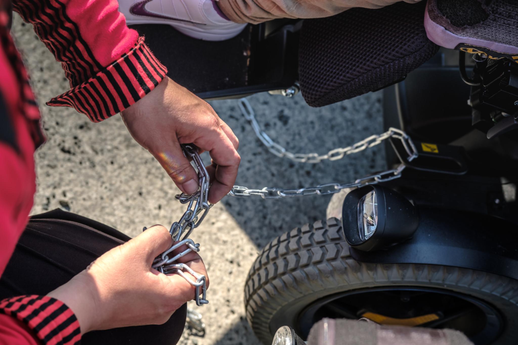 ein Rollstuhlrat ist zu sehen und eine weiße Hand, die eine Ankerkette um das Rollstuhlrad anbringt.