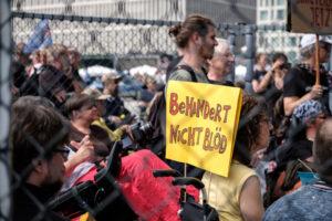 """Auf dem Bild sind ein paar weiße Menschen zu sehen. An einem Rollstuhl ist ein Schild mit der Aufschrift """"Behindert nicht blöd"""" zu sehen."""