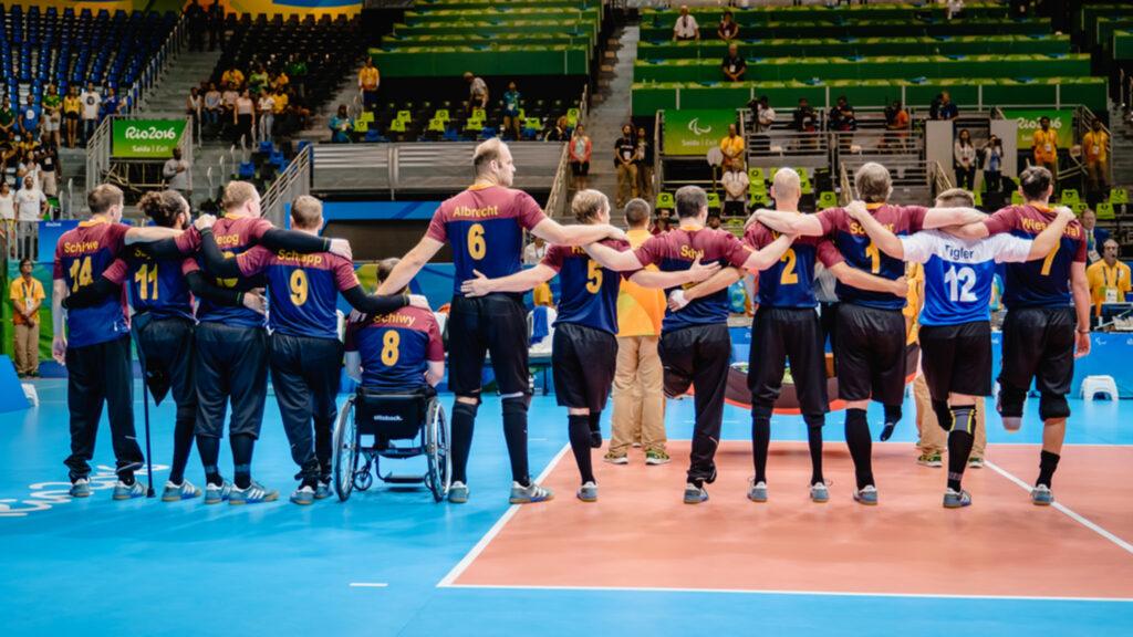 Mehrere Sportler mit Behinderung stehen in einer Turhalle nebeneinander Arm in Arm. Sie stehen mit dem Rücken zur Kamera.