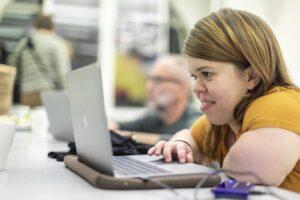 eine weiße kleinwüchsige frau arbeitet an einem laptop