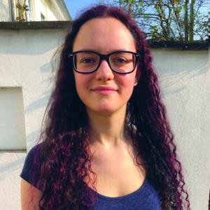 Xenja hat lange rot-braune Haare, trägt eine Brille und ein schwarzes T-shirt