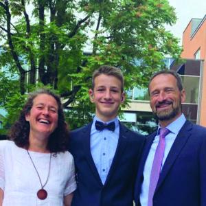 Ein junger Mann mit kurzen blonden Haaren steht zwischen seinen Eltern. Er trägt einen dunklen Anzug, ein hellblaues Hemd und eine schwarze Fliege. Seine Mutter ein weißes Kleid. Sein Vater einen dunklen Anzug, mit hellblauem Hemd und rosa Krawatte.