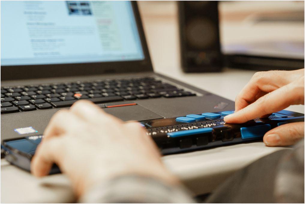 Heiko Kunert sitzt vor seinem Laptop, der mit Hilfstechnologien für blinde und sehbehinderte Menschen ausgestattet ist.