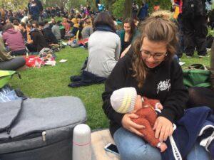 eine weiße frau sitzt auf einer wiese und hält ein baby im arm