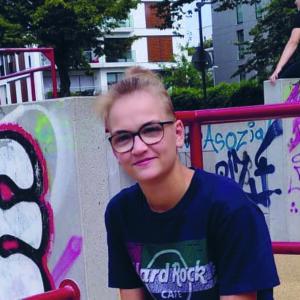 Paulina hat kurze blonde Haare, trägt ein schwarzes T-Shirt und sitzt vor einer Mauer mit Graffitti