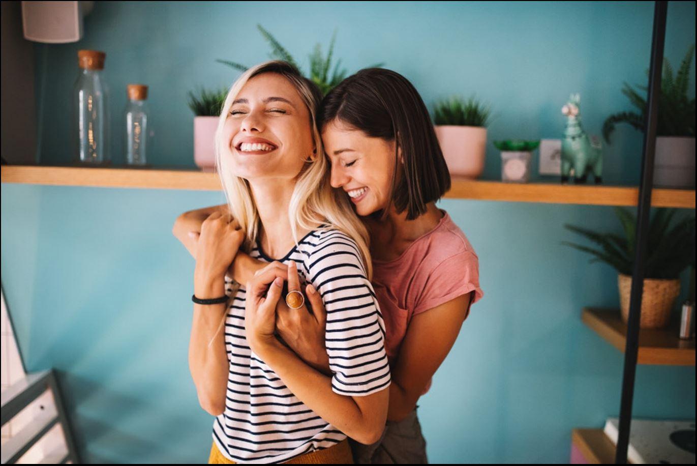 Zwei Frauen umarmen sich breit grinsend und halten dabei Händchen.