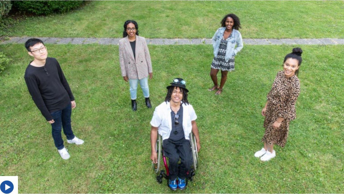 Drei Frauen und ein Mann stehen lächelnd mit etwas Abstand um einen grinsenden Mann im Rollstuhl herum. Vier der fünf jungen Menschen sind Schwarz.