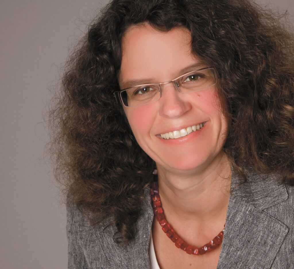 Claudia Becker hat schulterlange, braune, lockige Haare, trägt eine graue Jacke und eine rote Kette. Sie lächelt in die Kamera.