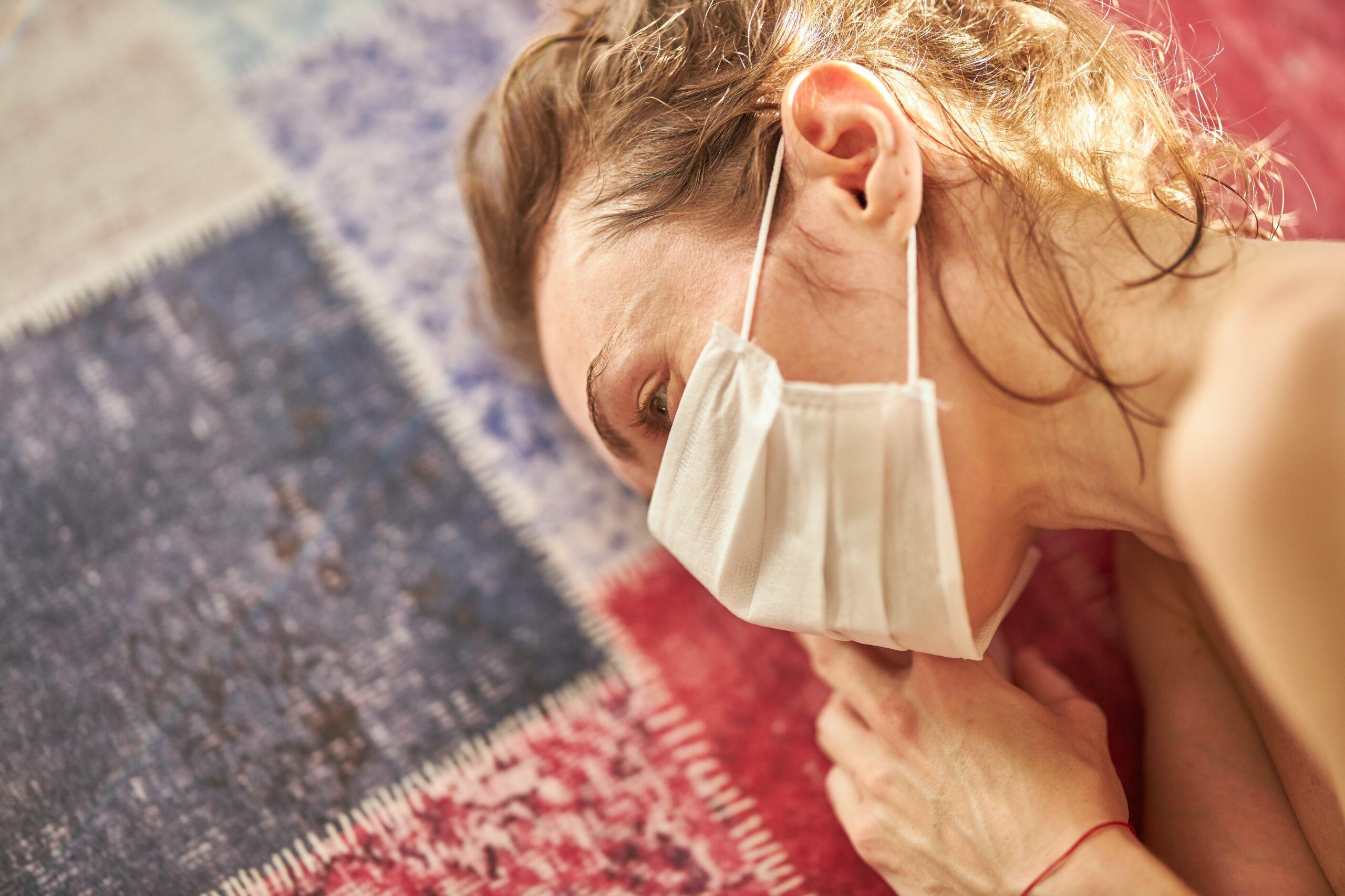 Eine Frau mit blonden Haaren liegt mit geschlossenen Augen auf dem Teppichboden. Sie hat einen weißen Mund-Nasen-Schutz auf.