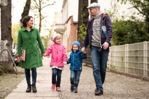 Eine Familie, bestehen aus Vater, Mutter Sohn und Tochter laufen Hand in Hand über den Bürgersteig. Die Tochter hat eine Behinderung.