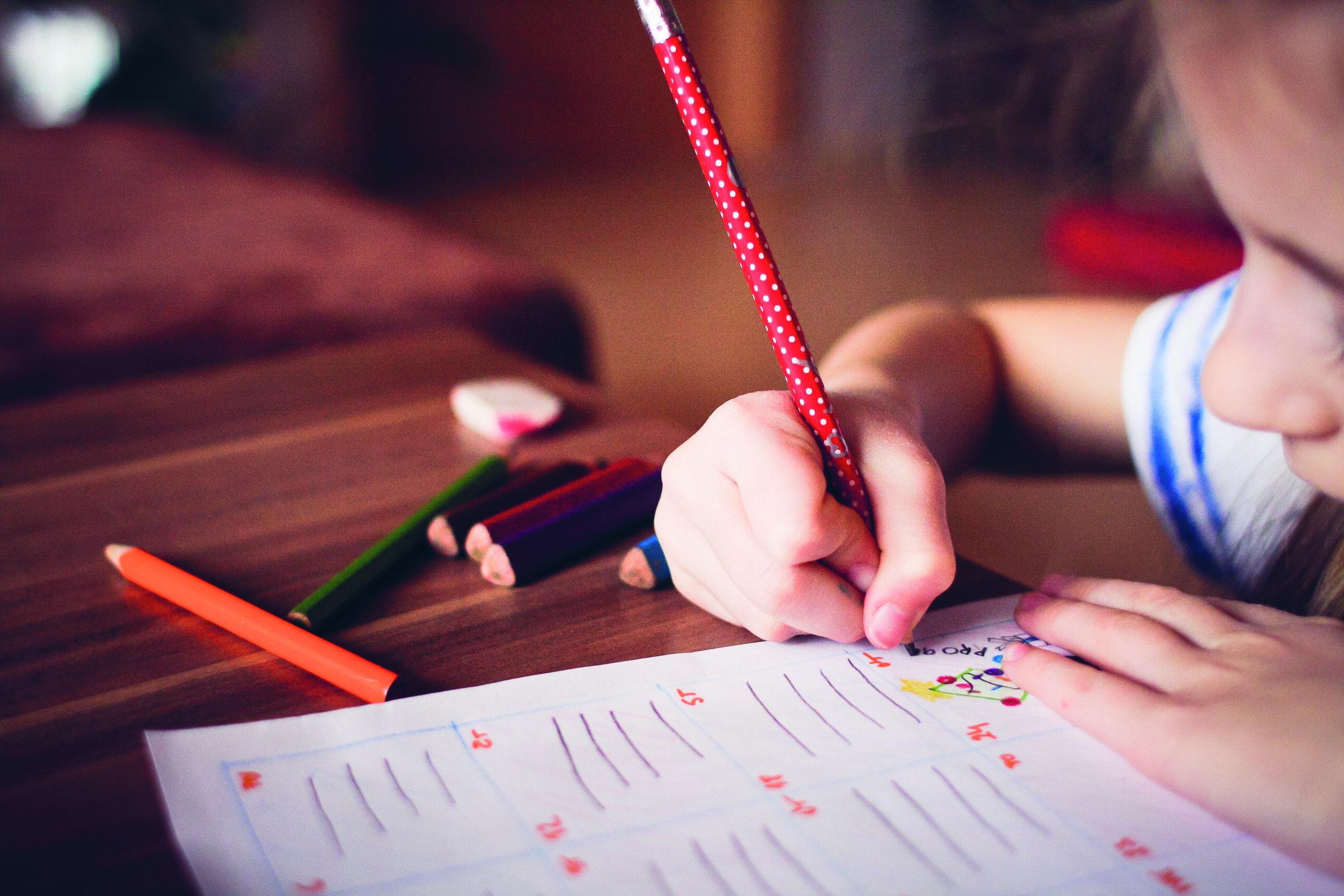 Ein Kind sitzt an einem Tisch und macht mit einem roten Bleistift Hausaufgaben.