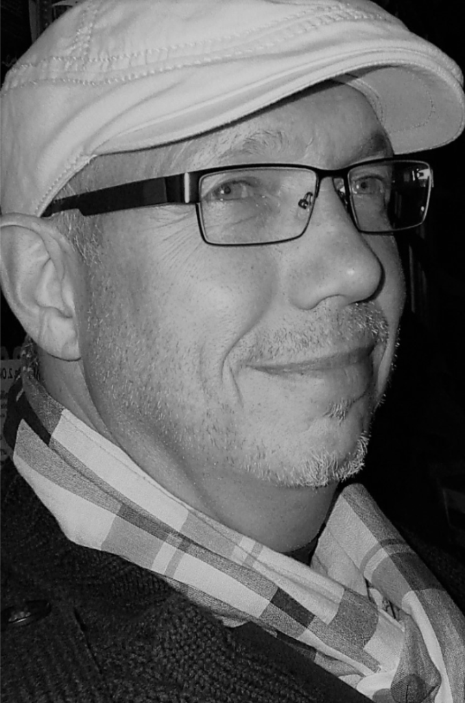 Schwarz-weiß Foto von Thorsten Kettritz. Er trägt eine brille und eine helle schlägermütze.