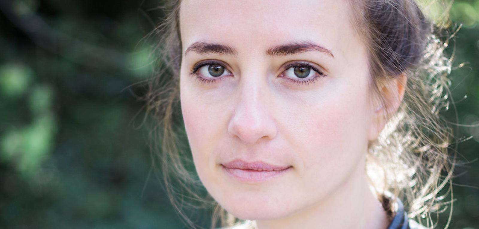 Das Gesicht einer weißen Frau mit grünen Augen und braunen Haaren schaut sanft in die Kamera. Es ist Anika Landsteiner.
