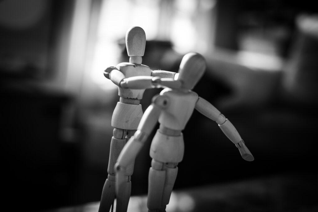 Schwarz-weiß Foto von zwei Holzfiguren. Die eine Figur würgt die andere.