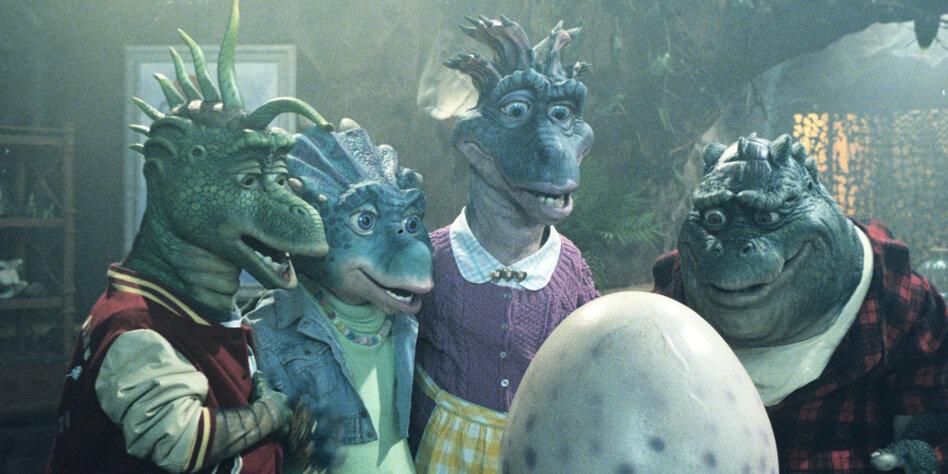 Die vier bläulichen Dinos aus der Sitcom Die Dinos der 90er stehen um ein großes weißes Ei versammelt und schauen es erwartungsvoll an.