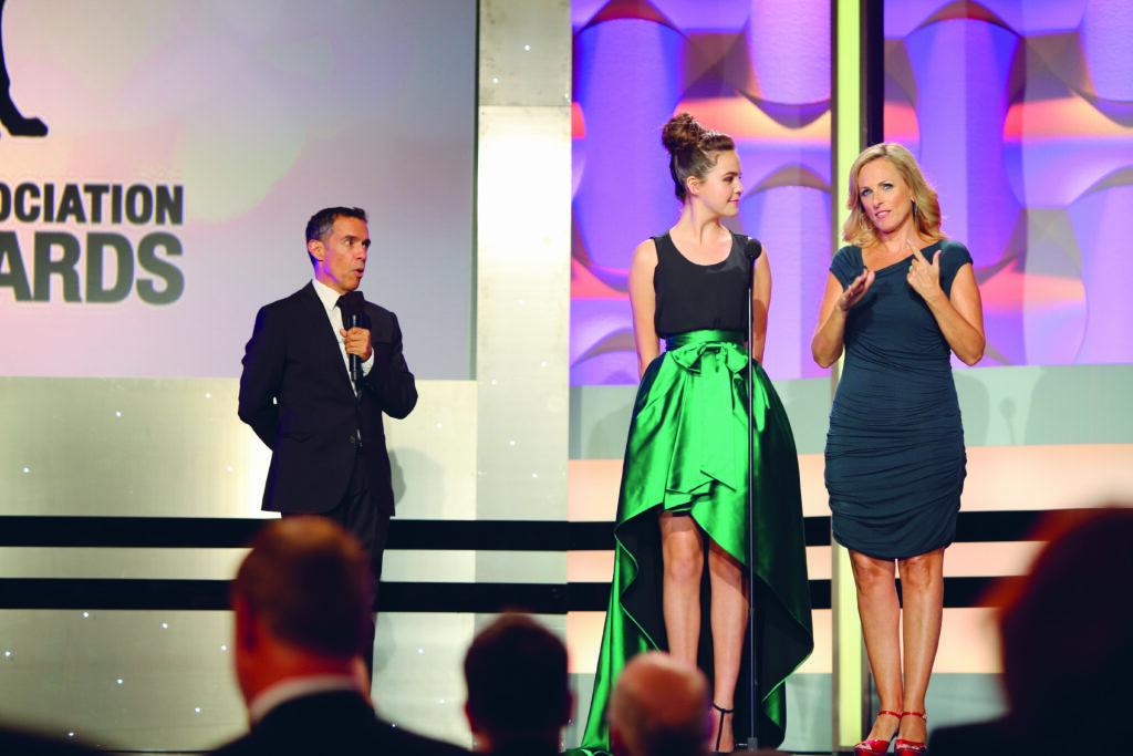 Marlee Matlin steht mit einer anderen Frau auf der Bühne. Abseits davon steht an Mann auf der Bühne mit einem Mikro in der Hand.
