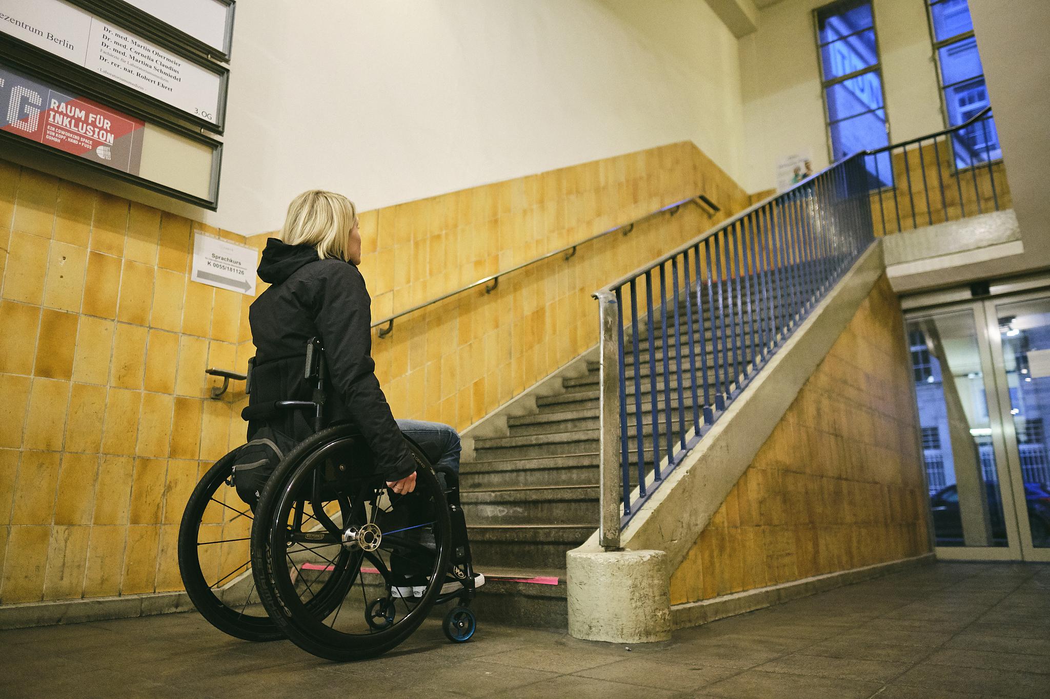 Eine Frau sitzt im Rollstuhl vor einer großen Treppe.