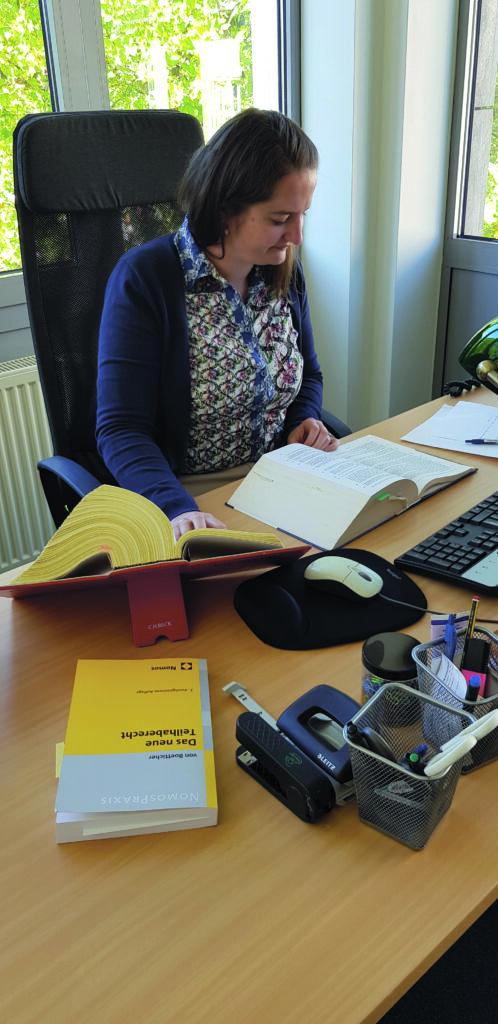 Foto von Mareike. Sie sitzt an ihrem Schreibtisch und ließt in einem dicken Buch.