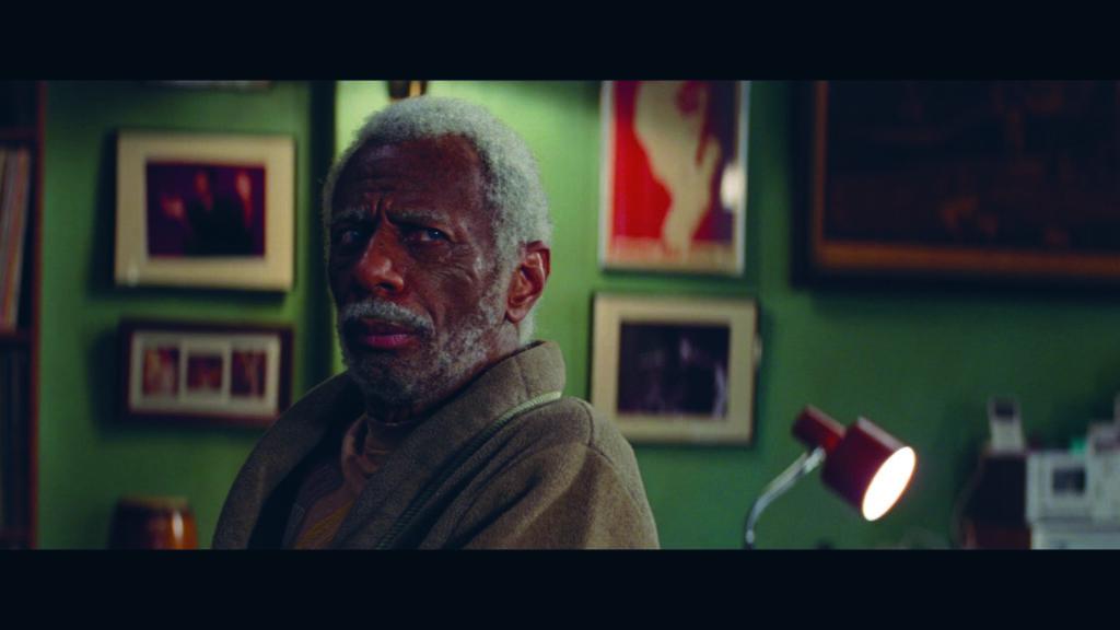 CJ Jomes ist ein alter, schwarzer Mann mit grauen kurzen Haaren und Bart und sitzt in einem wenig beuchtetem Zimmer auf einem Stuhl.