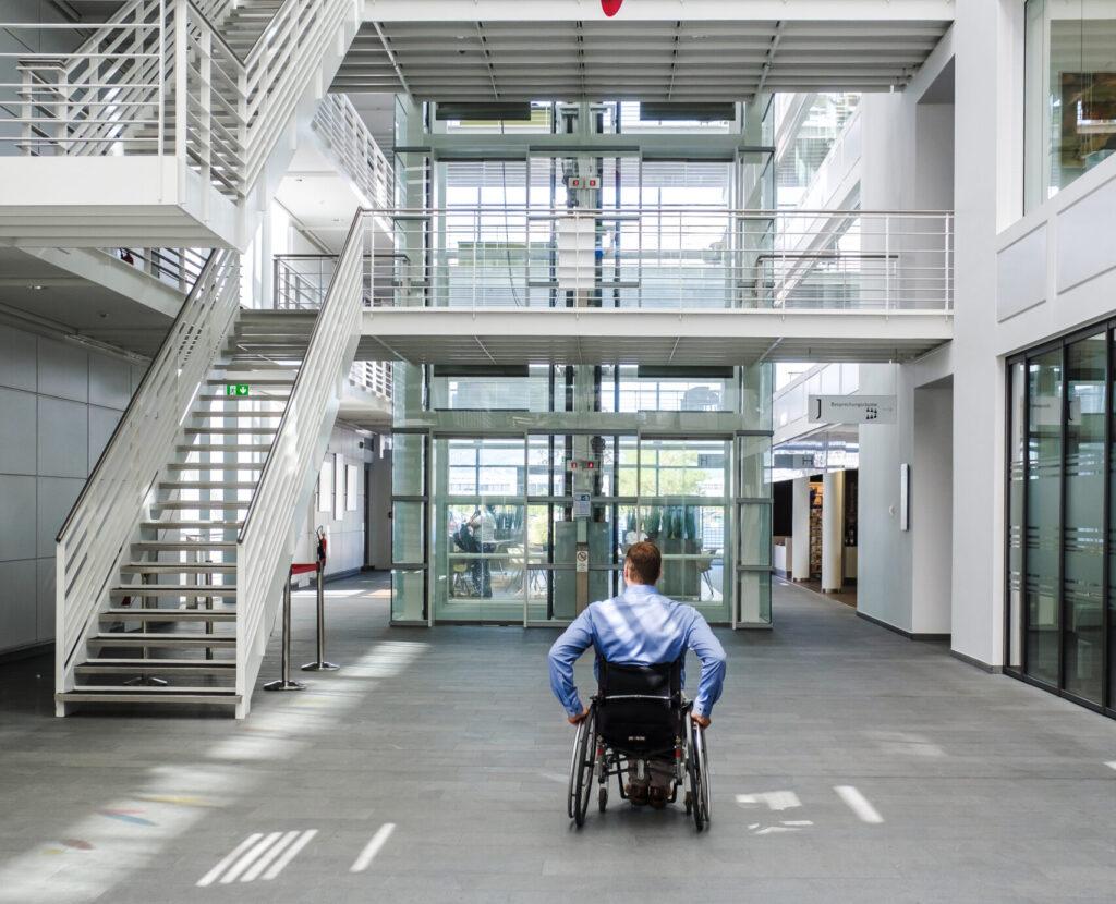Ein weißer Mann im Rollstuhl fährt in ein großes, modernes Foyer mit vielen Treppen.