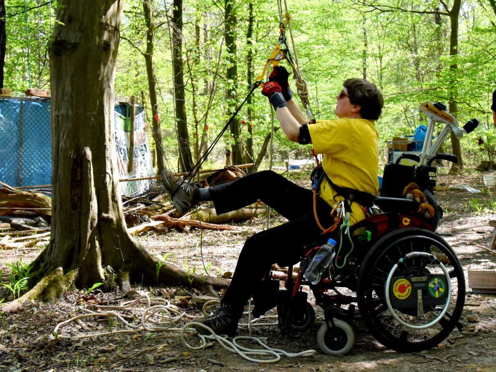 Cecile klettert im Wald aus ihrem Rollstuhl auf einen Baum.