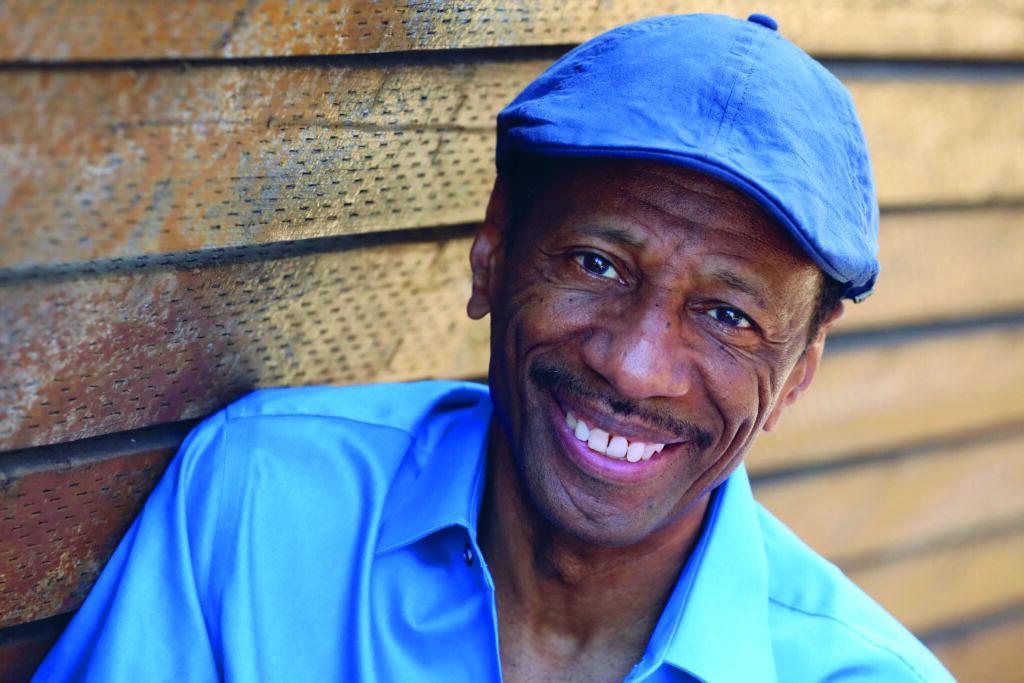 Foto von CJ JOnes. Er ist ein schwarzer, mittel allter Mann. Er trägt ein balues Hemd und eine blaue Mütze und lächelt in die Kamera.