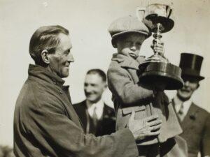 Ein altes Bild von einem alten Mann, der einen kleinen Jungen mit Pokal hochhält.