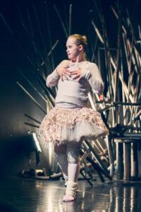 Eine weiße Tänzerin mit Downsyndrom legt ihre Hände auf ihren Oberkörper.