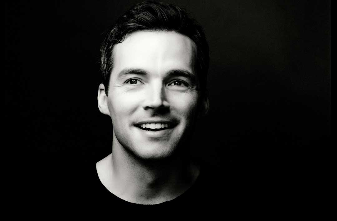 Eine Portrait Aufnahme von Ian Harding vor schwarzem Hintergrund in schwarz weiß. Ian ist ein weißer Mann mit braunen Haaren.