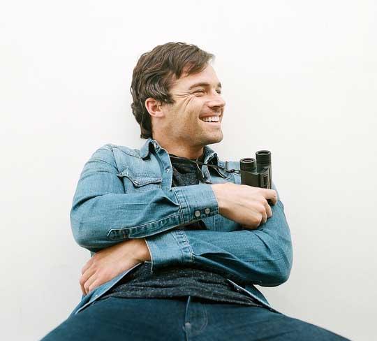 Ein Foto von Ian Harding: Ein weißer Mann mit braunen Haaren trägt eine Jeansjacke und hält ein Fernglas in der Hand. Er schaut amüsiert nach links.