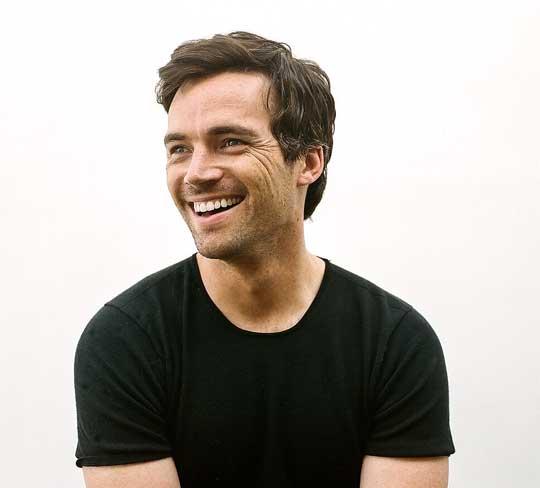 Ein Foto von Ian Harding: Ein weißer Mann mit braunen Haaren und blauen Augen trägt ein schwarze T-Shirt und schaut lächelnd nach links.