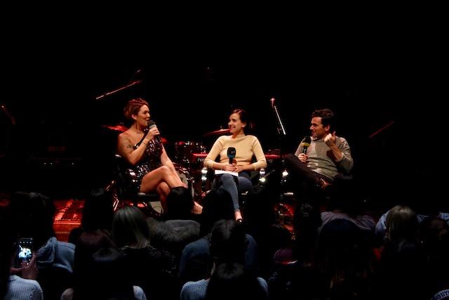 Auf einer Bühne sitzen zwei Frauen und ein Mann mit Mikrophonen und sprechen miteinander. Im Vordergrund sitzt Publikum.