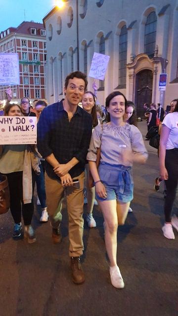 """Vor Demonstrierenden mit Schildern laufen Ian Harding und Susanne auf dem """"Walk of Lupus""""."""