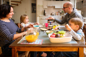 Eine weiße Familie sitzt gemeinsam am Tisch und isst Frühstück.