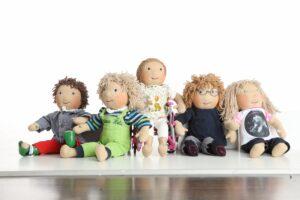 Fünf handgemachte Puppen mit Behinderungen sitzen nebeneinander. Einige tragen Orthesen, eine andere sitzt im Rollstuhl.