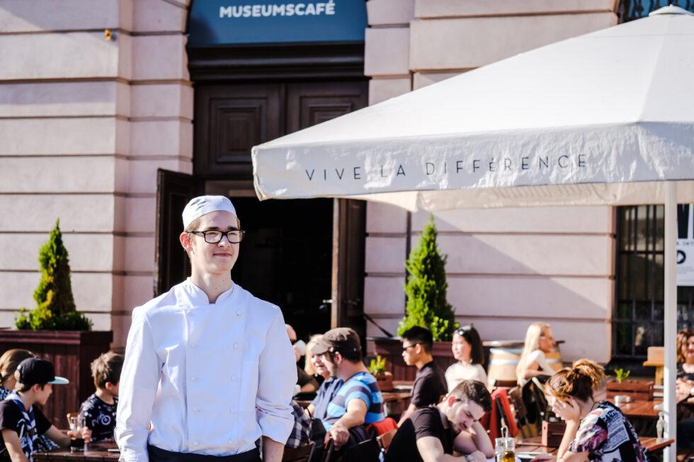 Ein junger weißer Mann in Kochkleidung steht lächelnd im Sonnenschein vor dem Museumscafe. Hinter ihm sitzen viele Gäste.