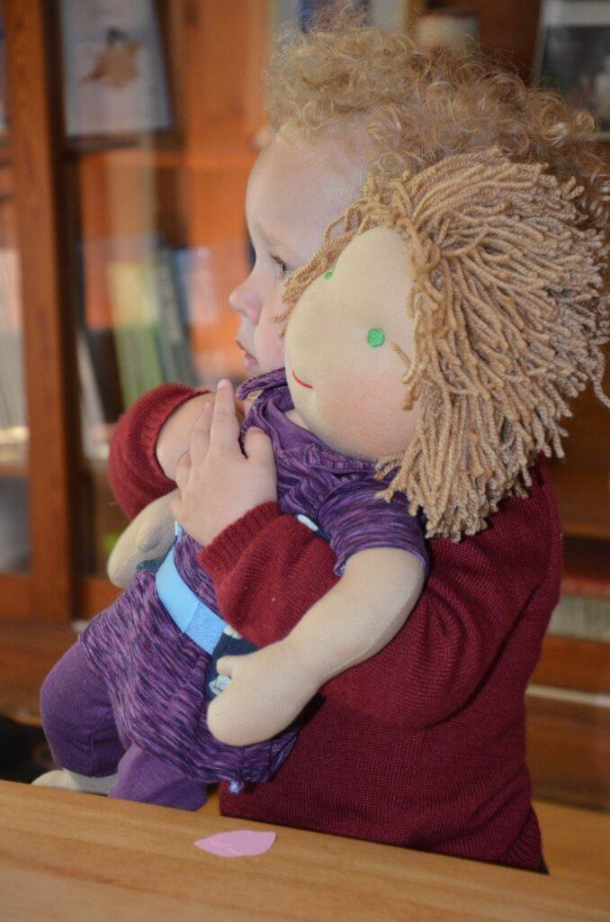 Ein Kleinkind mit blonden lockigen Haaren umarmt eine Puppe, die ihm ähnlich sieht.