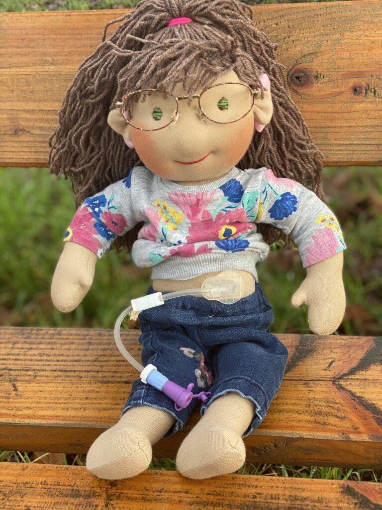 Eine handgemachte braunhaarige Puppe mit Magensonde und Brille sitzt auf einer Bank.