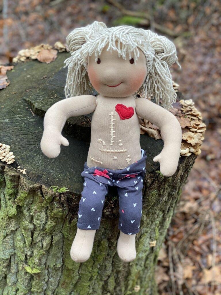 Eine handgemachte blonde Puppe ist Oberkörper frei und man sieht verschiedene Narben am Bauch.