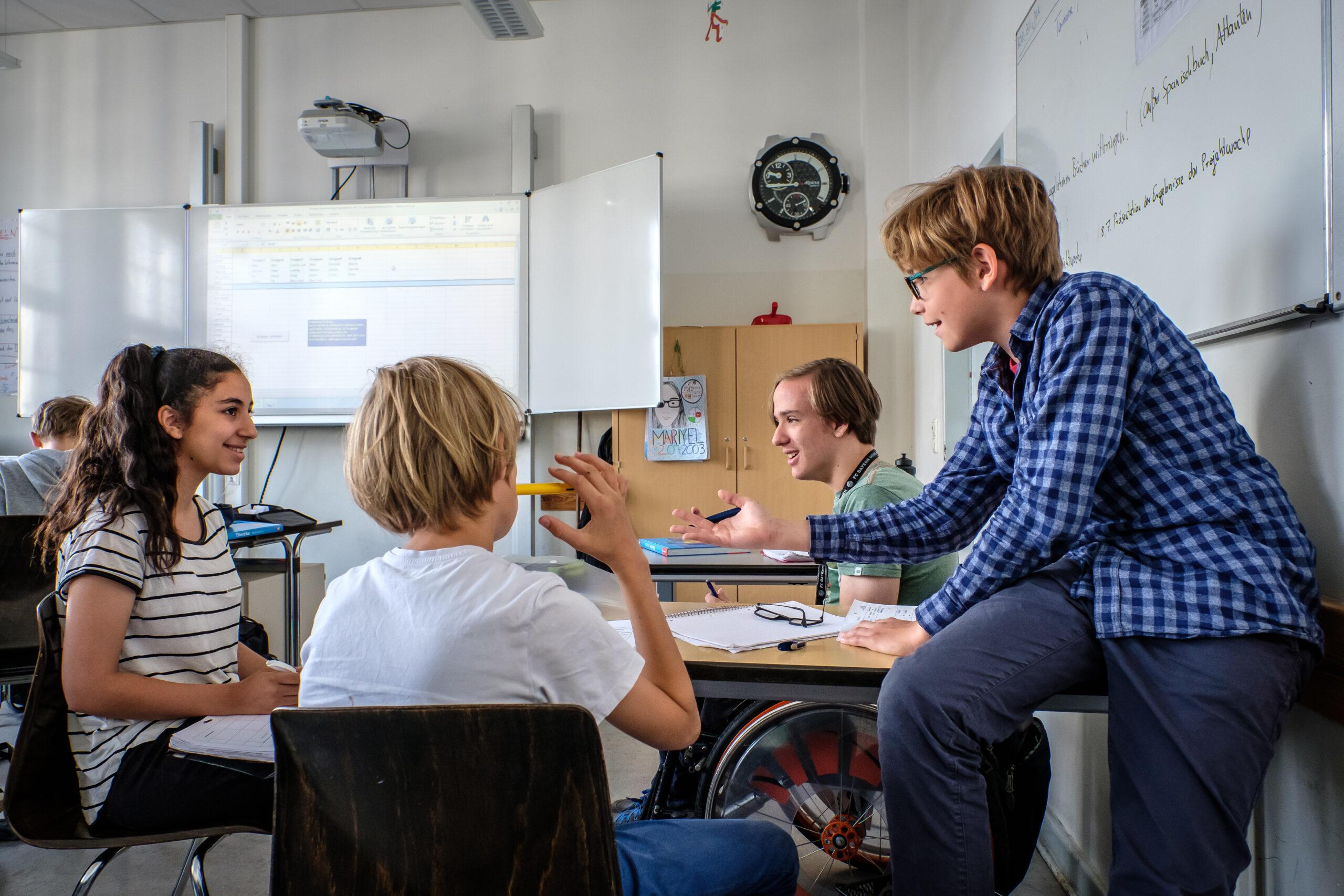 In einem Klassenraum sitzen drei Schüler:innen an einem Tisch mit einer Lehrkraft, die mit ihnen etwas bespricht.