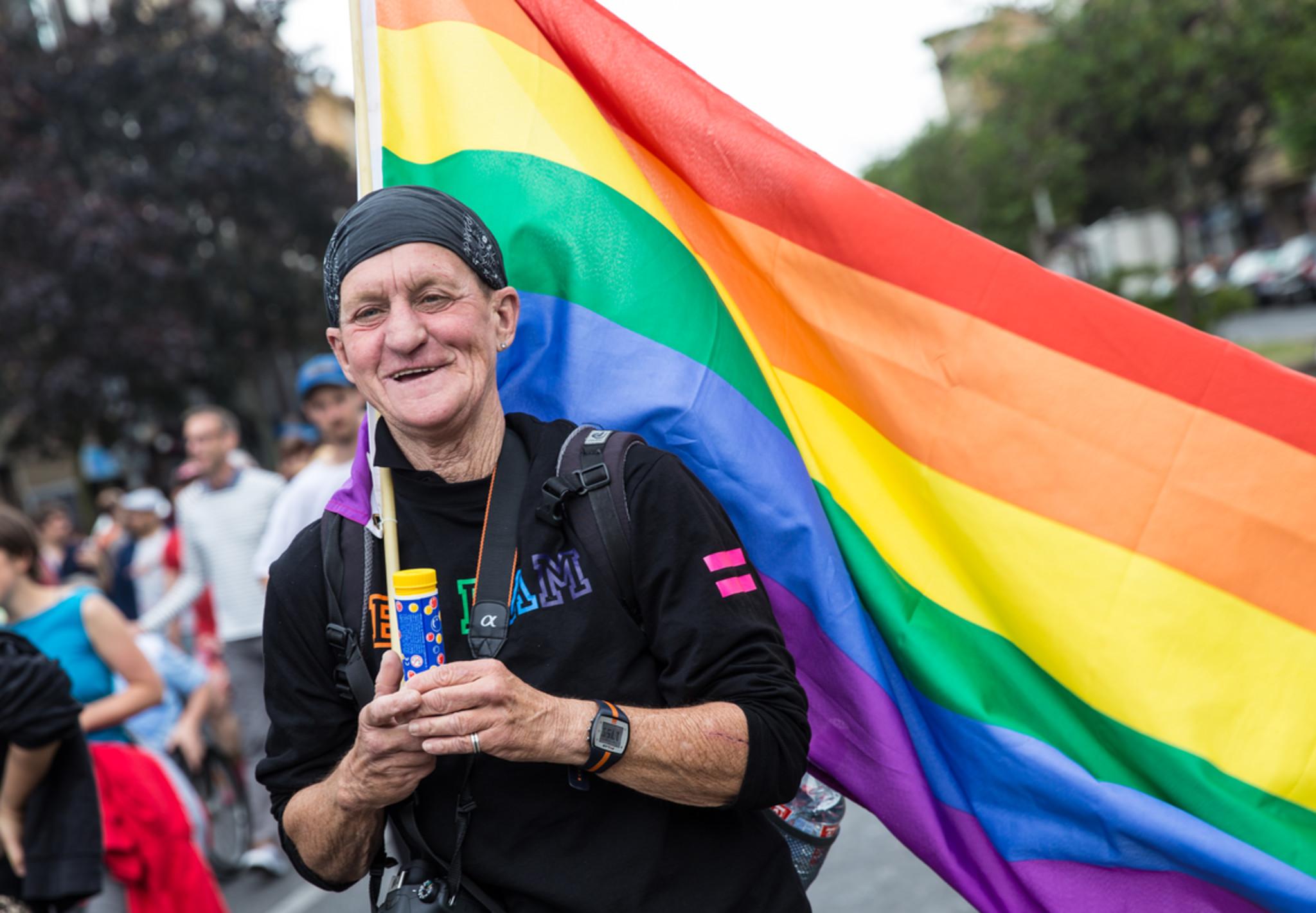 Ein älterer Mann hält auf einer Demonstration eine Regenbogenfahne in der Hand und lächelt in die Kamera.