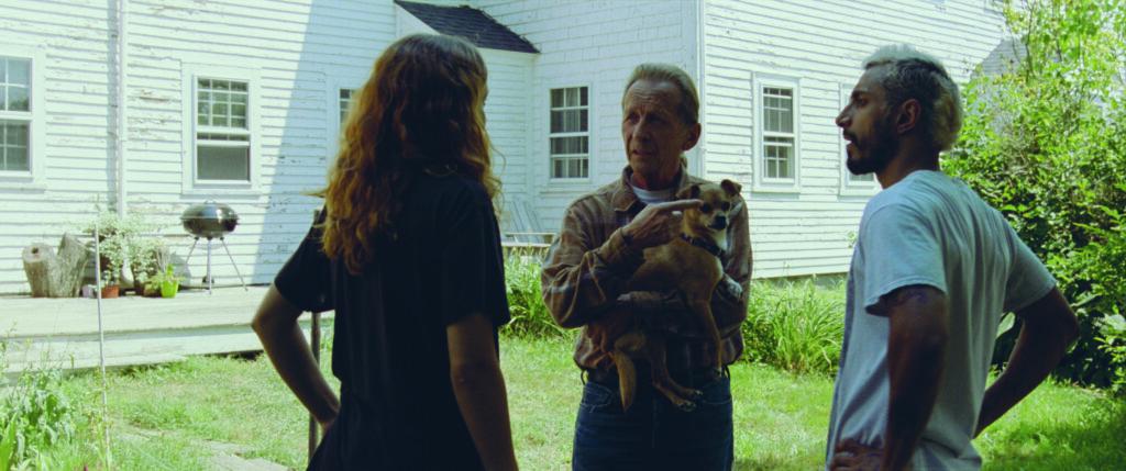 Eine Frau und wei Männer stehen vor einem weißen Haus und sprechen Gebärdensprache.