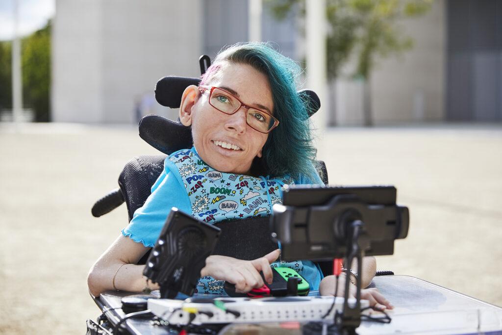 Eine Frau sitzt im Rollstuhl. Sie hat einen sidecut und blau gefärbte Haare. Vor Ihr sind verschiedene Spiele-Controller.