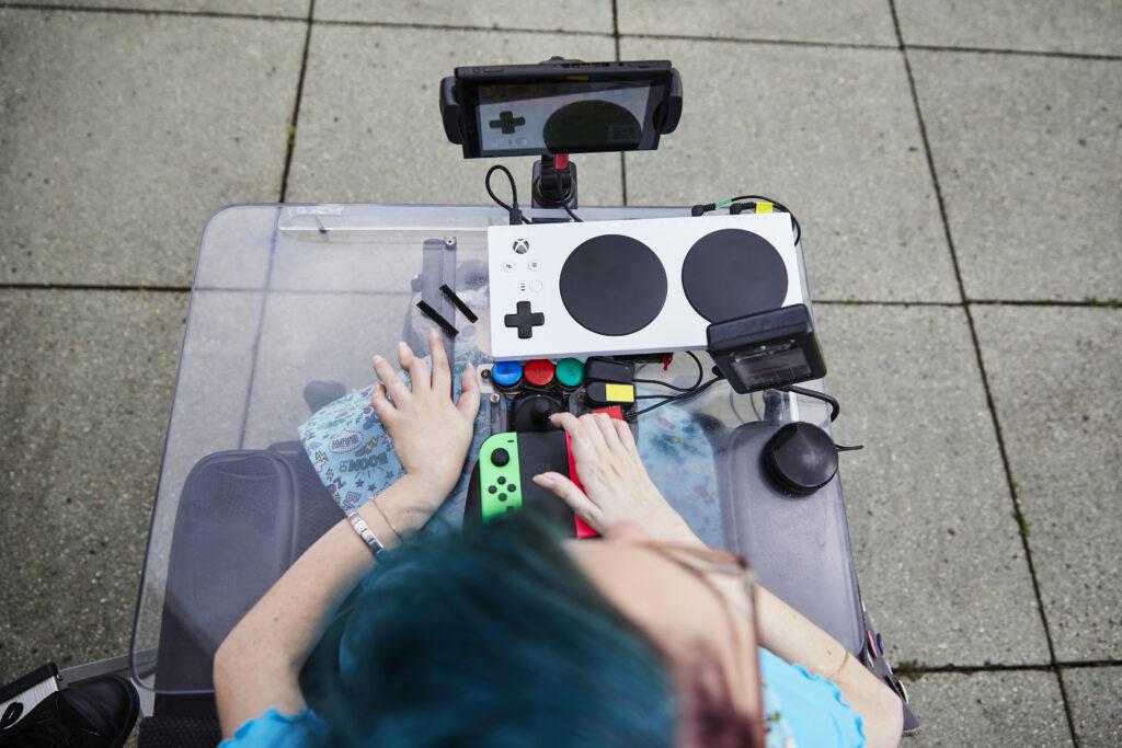 Aus der Vogelperspektive blickt man auf Melanie Eilert, eine weiße Frau mit blauen Haaren, die im Rollstuhl sitzt und diverse Gaming-Controller auf ihrem Tisch hat.